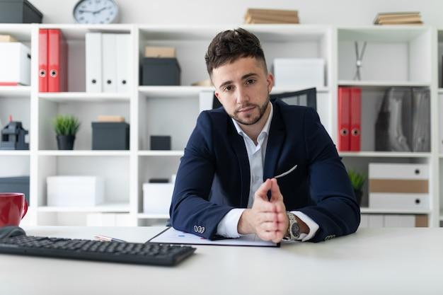 Un jeune homme assis dans le bureau devant un bureau et travaillant avec des documents.