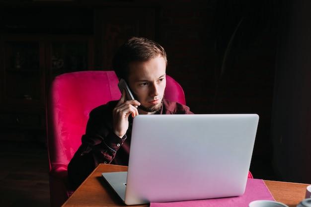 Jeune homme assis dans un fauteuil et parler au téléphone