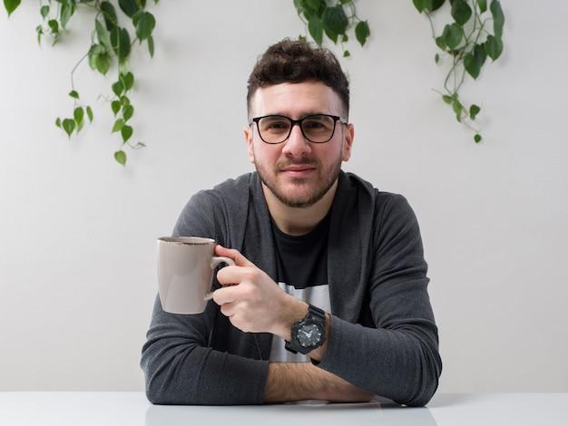 Jeune homme assis dans des lunettes montres veste grise tenant sa tasse de café avec plante sur blanc
