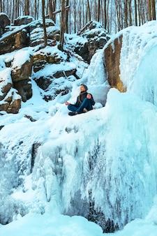 Un jeune homme assis dans la neige congère dans la forêt et regardant la rivière d'hiver
