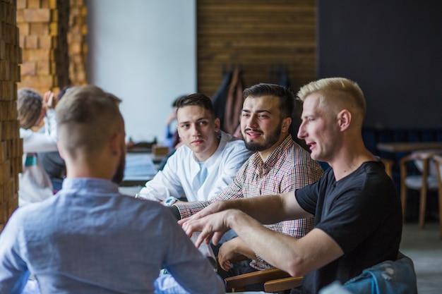 Jeune homme assis dans un restaurant expliquant la stratégie à ses amis