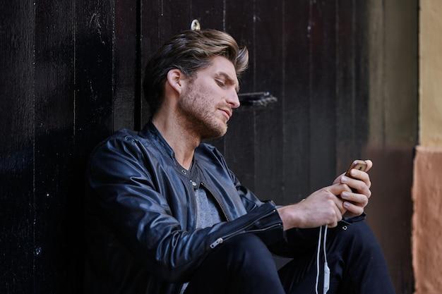 Jeune homme assis dans la rue