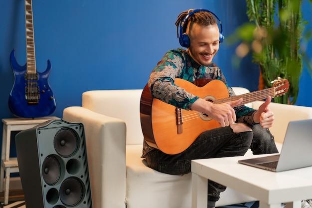 Jeune homme assis dans sa chambre et regarder le tutoriel de guitare sur ordinateur portable se bouchent