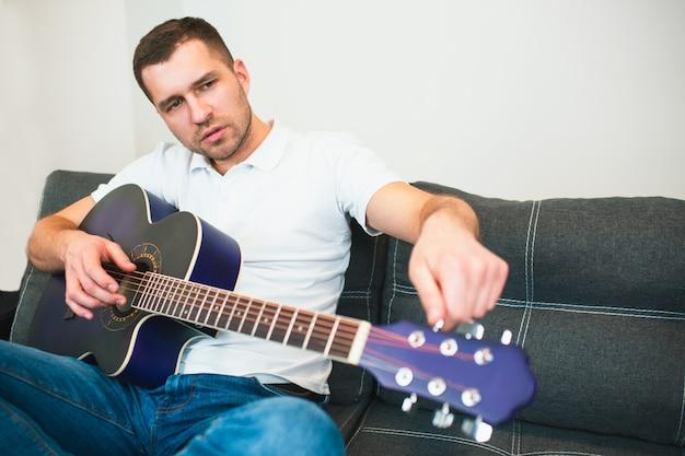 Jeune homme assis dans la salle de réglage des cordes pour mieux jouer sur la guitare acoustique. musicien solo apprenant à bien jouer.
