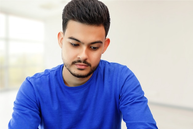 Un jeune homme assis devant un ordinateur portable à la recherche de travail, faisant des affaires sur internet. à la lumière