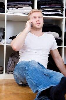 Jeune homme assis devant sa garde-robe.