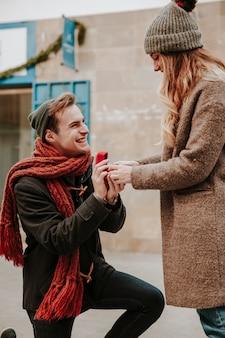 Jeune homme assis à genoux et proposant à la petite amie