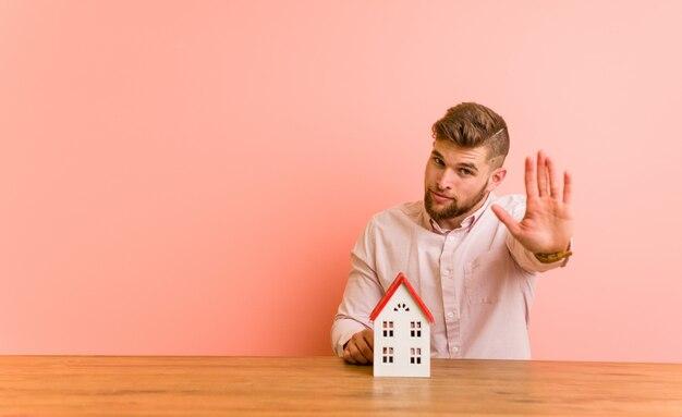 Jeune homme assis avec une icône de la maison debout avec la main tendue montrant le panneau d'arrêt, vous empêchant