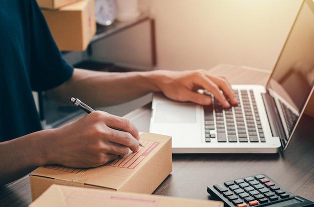 Jeune homme assis à la maison emballant à envoyer par la poste prêt à écrire l'adresse de contact client à partir du cahier pour envoyer la destination.