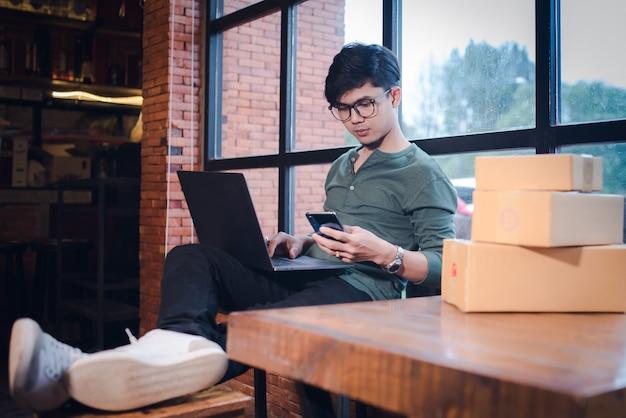 Jeune homme assis avec un ordinateur et un téléphone mobile sur un plancher en bois avec parcelle concept d'idées de vente en ligne.