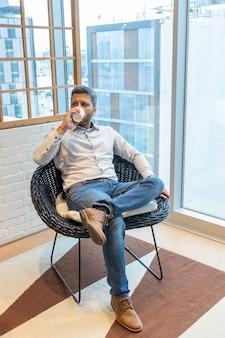 Jeune homme assis et pensif ayant un café noir