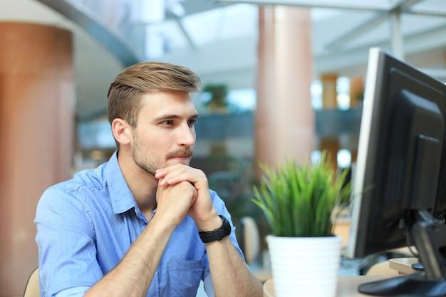 Jeune homme assis et regardant un écran d'ordinateur tout en travaillant au bureau.