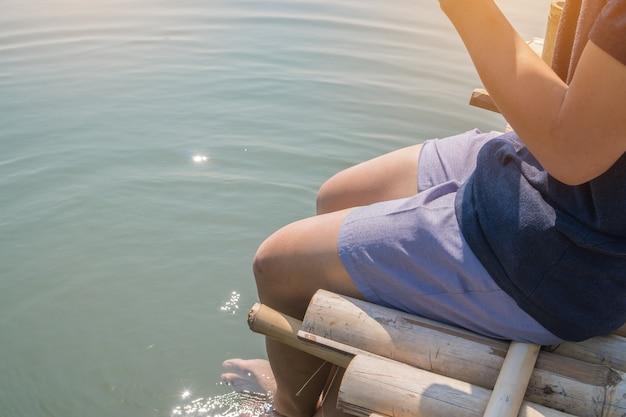 Jeune homme assis s'assouplit pour faire pivoter des pieds près de la surface de l'eau sur le bord latéral du bois