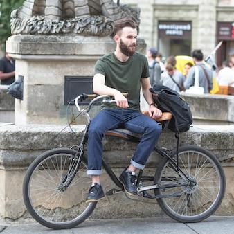Jeune homme assis avec sa bicyclette à l'extérieur