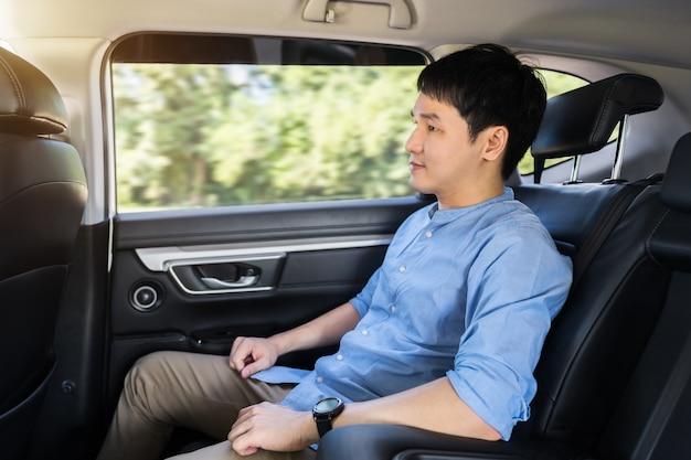 Jeune homme assis sur le siège arrière de la voiture