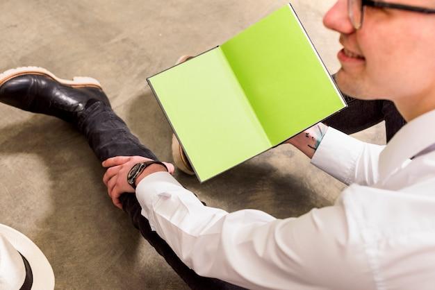 Jeune homme assis sur un sol en béton tenant un livre ouvert à la main
