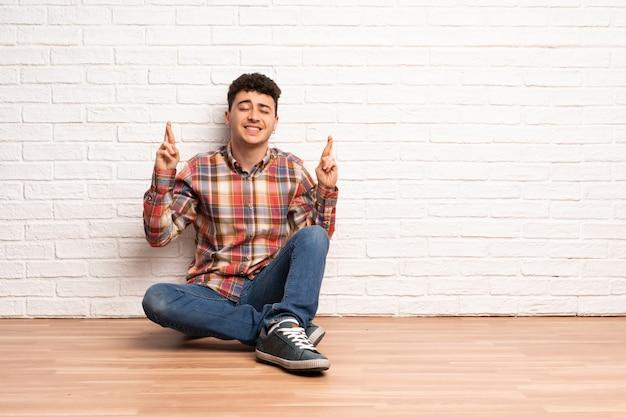 Jeune homme assis sur le sol avec les doigts qui se croisent et souhaitant le meilleur