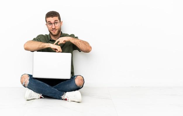 Jeune homme assis sur le sol faisant le geste d'être en retard