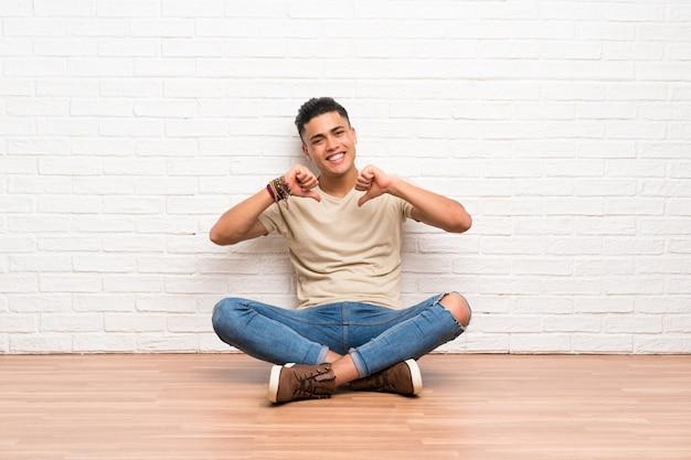 Jeune homme assis sur le sol, fier et satisfait