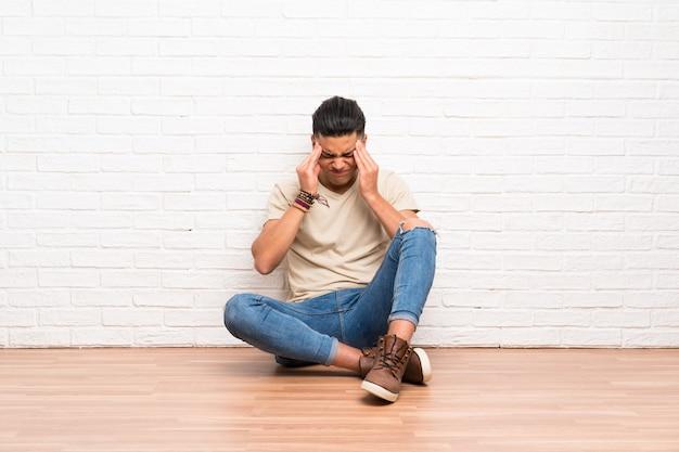Jeune homme assis sur le sol, mécontent et frustré par quelque chose. expression faciale négative