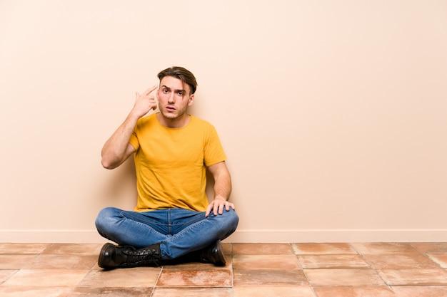 Jeune homme assis sur le sol montrant un geste de déception avec l'index