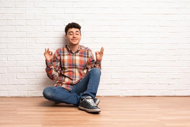 Jeune homme assis sur le sol en pose zen