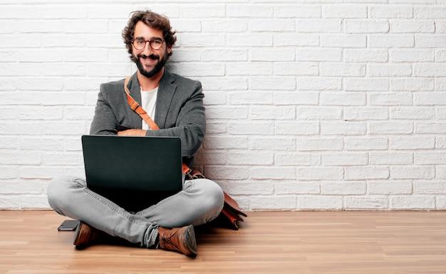 Jeune homme assis sur le sol avec un regard fier, satisfait et heureux sur le visage