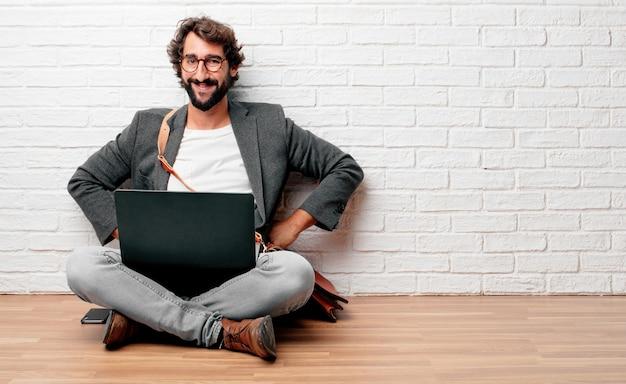 Jeune homme assis sur le sol avec un regard fier, satisfait et heureux