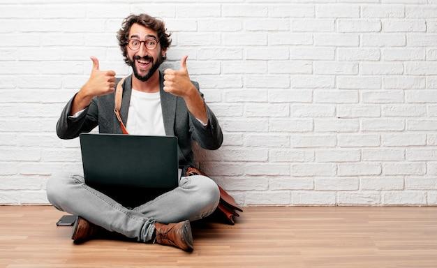 Jeune homme assis sur le sol avec un regard satisfait, fier et heureux avec le pouce en l'air
