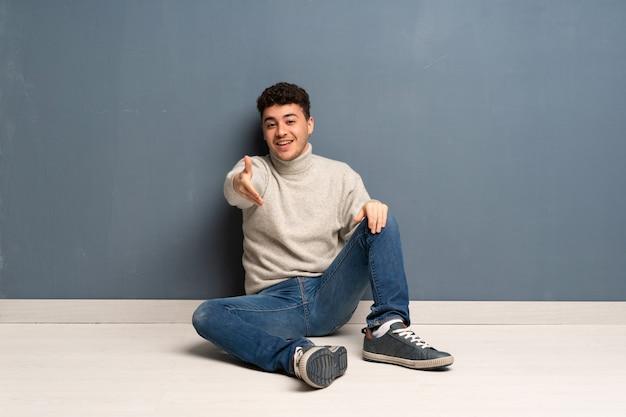 Jeune homme assis sur le sol se serrant la main pour avoir conclu une bonne affaire