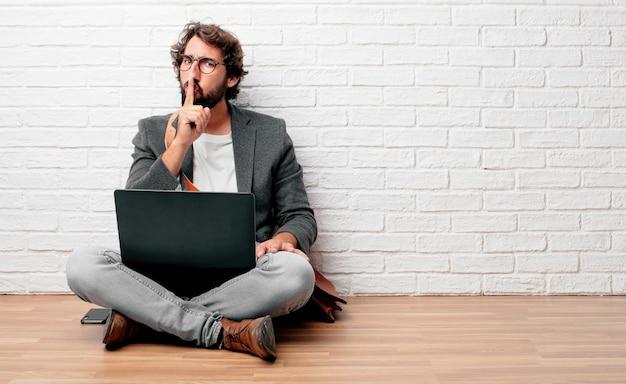 Jeune homme assis sur le sol en souriant, avec l'index devant la bouche