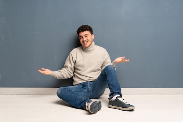 Jeune homme assis sur le sol en souriant