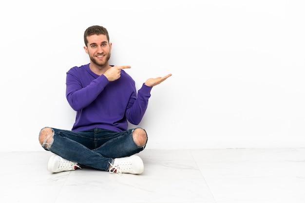 Jeune homme assis sur le sol tenant un espace de copie imaginaire sur la paume pour insérer une annonce