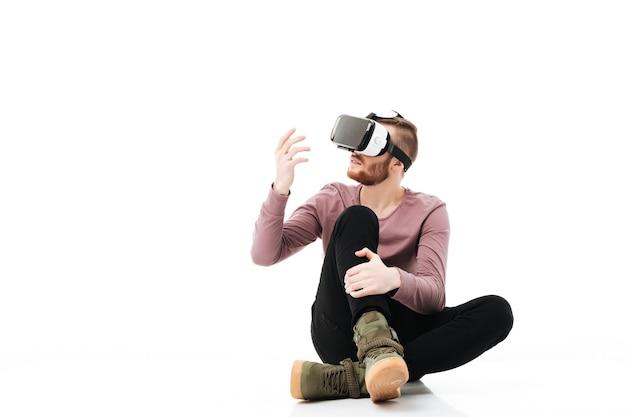 Jeune homme assis en studio et jouant avec des lunettes de réalité virtuelle