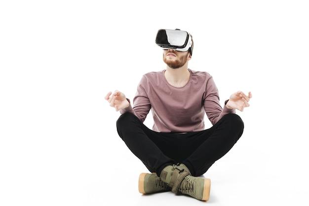 Jeune homme assis en studio et méditer tout en utilisant des lunettes de réalité virtuelle isolées
