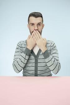 Jeune homme assis à table couvrant la bouche isolée sur bleu. je ne peux rien dire