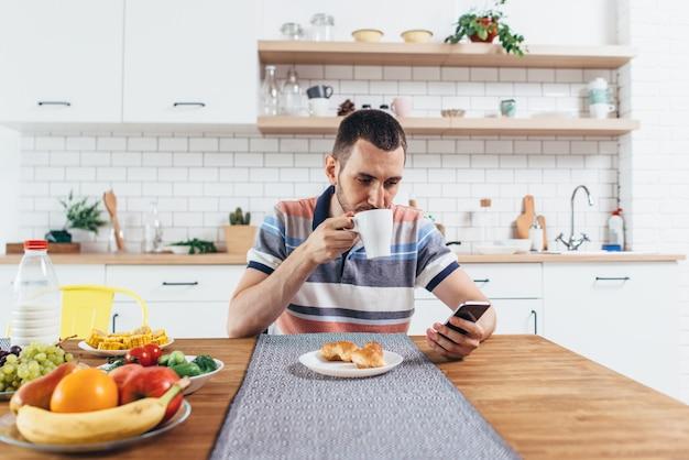Jeune homme assis à table dans la cuisine avec une tasse de café à l'aide de téléphone mobile.