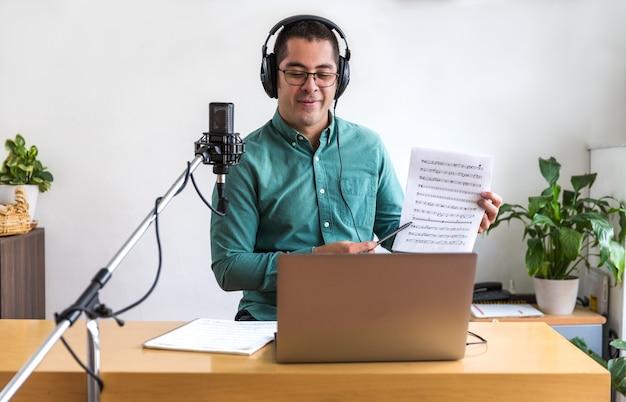 Jeune homme assis à la table avec un ordinateur portable il a des écouteurs et un microphone, il enseigne la musique live