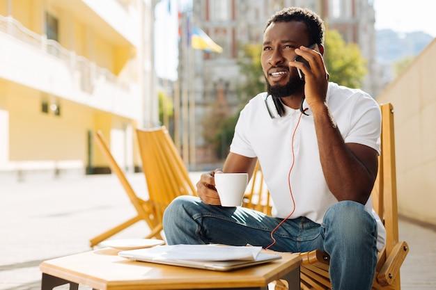 Jeune homme assis sur une terrasse et prendre un café