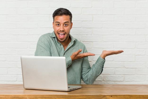 Jeune homme assis travaillant avec son ordinateur portable excité tenant quelque chose sur la paume