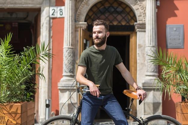 Jeune homme assis à vélo à l'extérieur