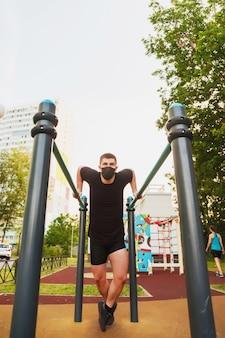 Jeune homme, un athlète engagé sur des barres asymétriques