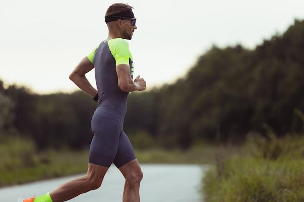 Jeune homme, athlète masculin de triathlon participant à une compétition sportive à l'extérieur