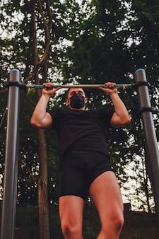 Jeune homme, athlète tire sur la barre. il porte un masque médical noir