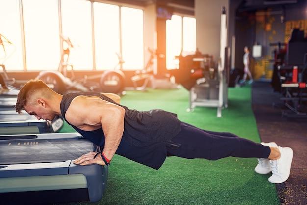 Jeune homme athlétique faisant des pompes dans une salle de sport