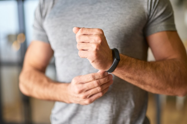 Jeune homme athlétique mettant une montre intelligente sur son poignet