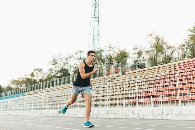 Jeune homme athlétique qui court sur le stade le matin