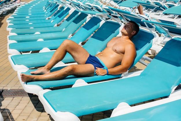 Un jeune homme athlétique sourit joyeusement et prend un bain de soleil sur une chaise longue par une journée ensoleillée. bonnes vacances vacances. vacances d'été et tourisme.