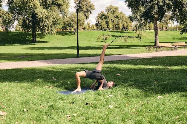 Jeune homme athlétique en tenue de sport, faire du yoga dans le parc
