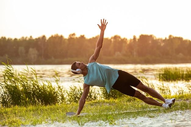 Un jeune homme athlétique travaillant à écouter de la musique au bord de la rivière en plein air